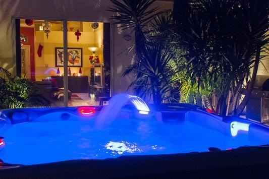 customer image of their hot tub at night with blue lighting and the waterfeature active