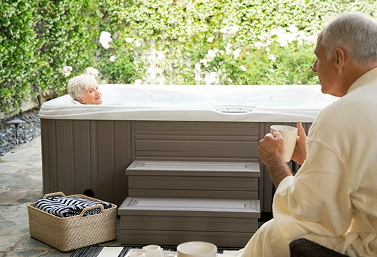 a couple relaxes on a patio with a hot tub drinking coffee