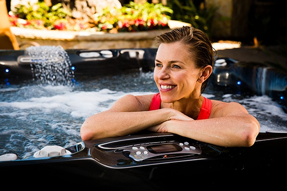 a woman soaks in her hot tub confident in the expert advice about hot tub water care maintenance