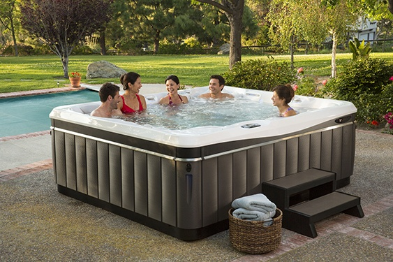 friends improve their relationship with a soak in a utopia cantabria hot tub on a beautiful sunny backyard patio