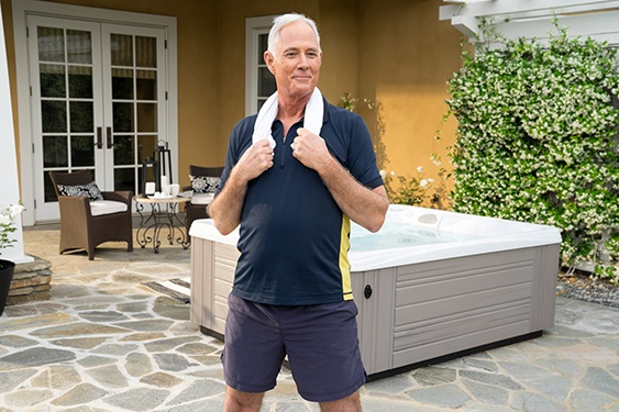 a man stands in front of his hot tub more quickly recovering from a workout with hot tub use