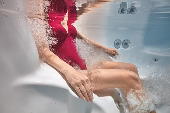 an underwater image of a lady in a red bathing suit relaxing in the massage jets of her hot tub