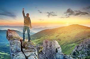 A young man stands on a mountain top at sunrise showing that he has found a way to boost his energy level