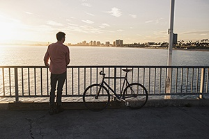 a man stands on a bridge overlooking a river while traveling with his bicycle