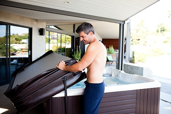 A man demonstrates how a hot tub cover lifter can make your hot tub more energy efficient and extend the life of your hot tub and your hot tub cover
