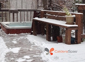 a hot tub on a snowy deck demonstrates you can use a hot tub in the winter