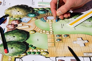 an artists hand works on a colorful architectural plan for a backyard design