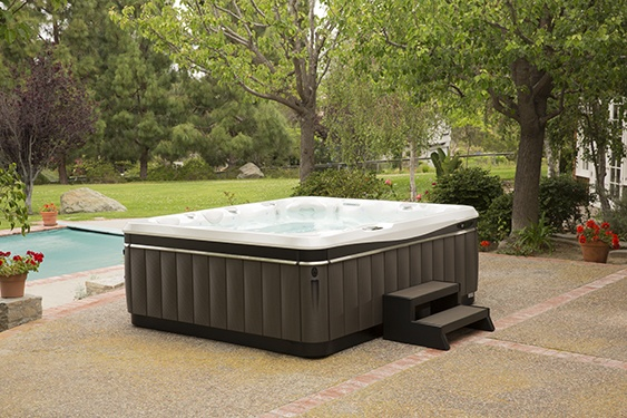 an image of a Caldera spa on a beautiful backyard patio with low maintenance and low cost