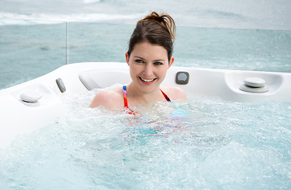 a lady relaxes in a utopia Tahitian hot tub with an arctic white color shell and a slate cabinet