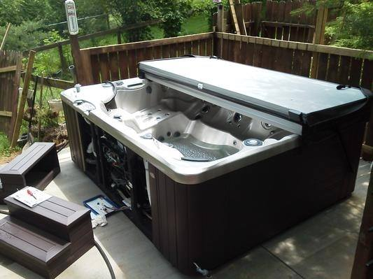 a hot tub on a deck with the maintenance access panel exposed for easy reach