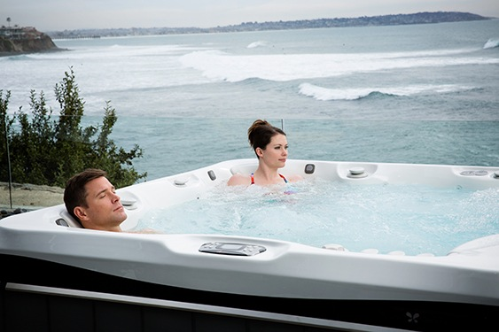 a couple soaks on an oceanside patio in their hot tub for better sleep