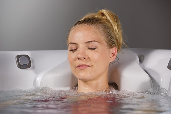 a woman uses warm water hot tub therapy as a natural sleep aid