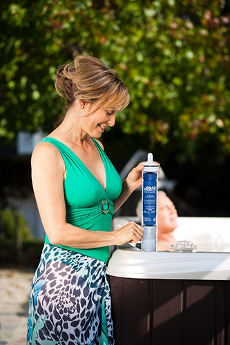 a photograph of a lady changing out her frog filter cartridge on a paradise makena hot tub with an espresso colored cabinet