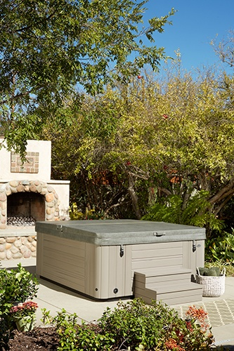 a photograph of a paradise martinique spa with coastal gray colored cabinet and a spa cover in a beautiful back yard with a barbecue pit