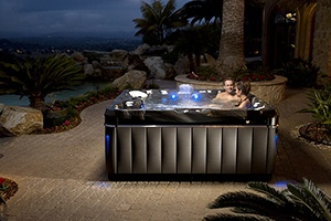 a couple enjoys a romantic soak in a hot tub in their own backyard