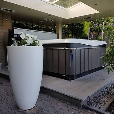 a utopia hot tub sits under a portico for protection from the weather