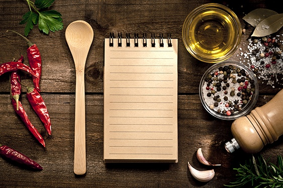 an appetizing counter top containing a recipe pad, spcies and peppers as well as a wooden spoon