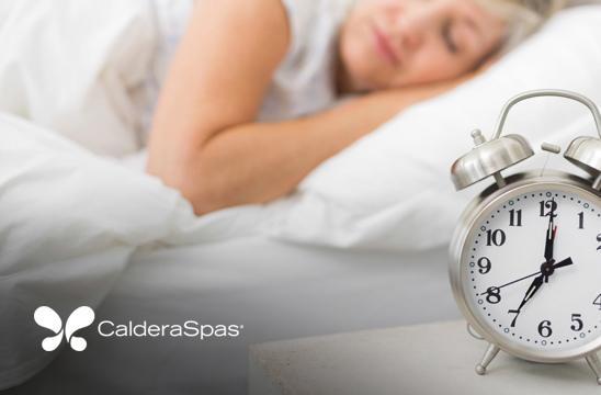 a woman sleeps with an alarm clock to keep a regular sleep cycle