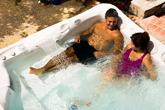 a couple wears old swim suits in their hot tub after rinsing well