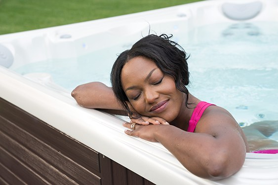 a woman soaks in a hot tub before bed to fall alseep fater