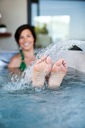 A lady stretches her legs into the waterfall feature of her Caldera spa