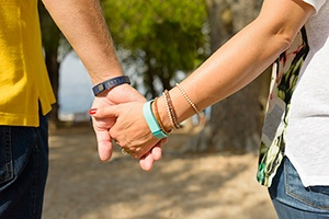 couple holding hands wearing new activity monitors