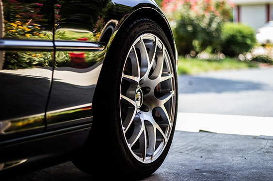 an image of a tire on a black car is used to support a discussion comparing auto maintenance to hot tub maintenance and comparing the benefits