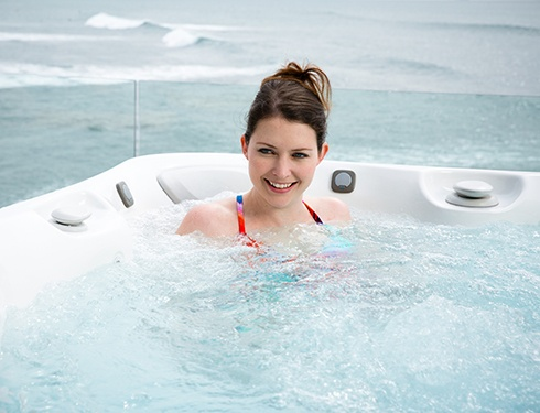 woman enjoys a hot tub with bromine water care system