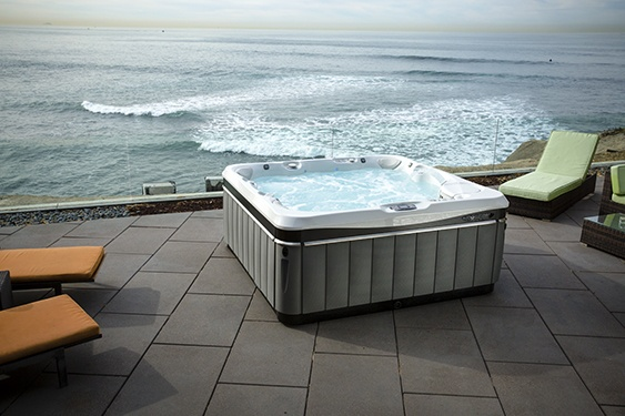 a utopia tahitian hot tub jacuzzi sits perched on a cliffside patio overlooking the ocean