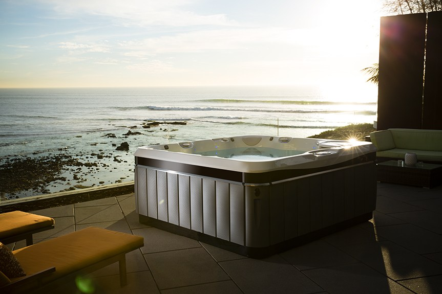 a utopia tahitian hot tub sits on the edge of an oceanside patio as the sun sets over the water
