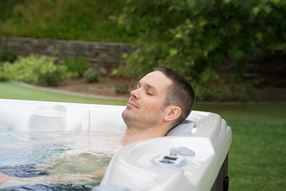 a man uses warm water therapy in his hot tub to sleep better