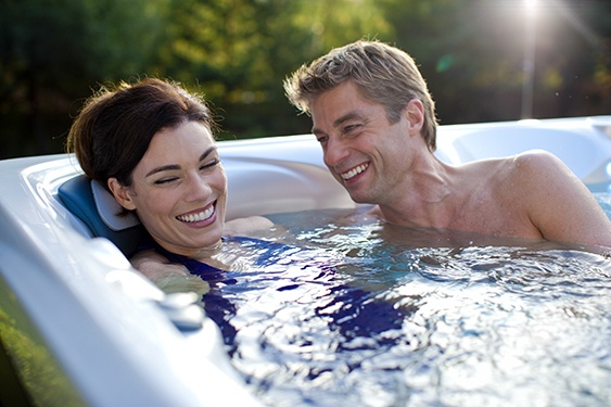 A couple talks and laughs and discusses concerns about a hot tub purchase