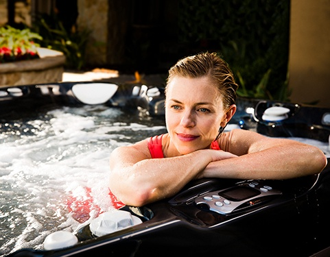 A woman gazes from the comfort of her hot tub contemplating the best hot tub features