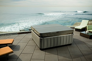 a hot tub sits on a patio cliff overlooking a dramatic ocean scene