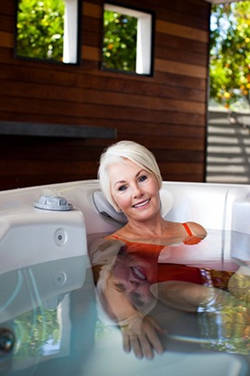 a woman relaxes in clear clean healthy hot tub spa water