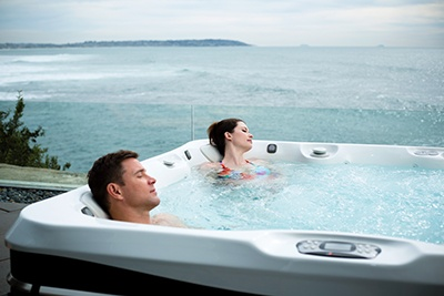 A couple relaxing in a hot tub with soothing jets