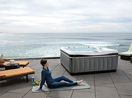 an image of a lady praciticing yoga with her Utopia spa in the foreground