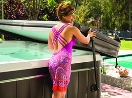 a woman in a colorful bathing suits easily opens her hot tub cover with a hot tub cover lifter
