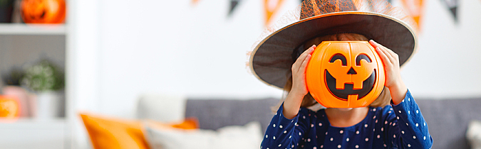 Young girl in witch hat with a pumpkin