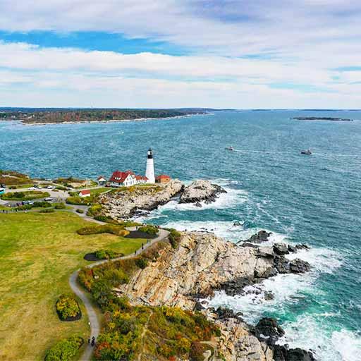 Maine lighthouse, rocks, and ocean.