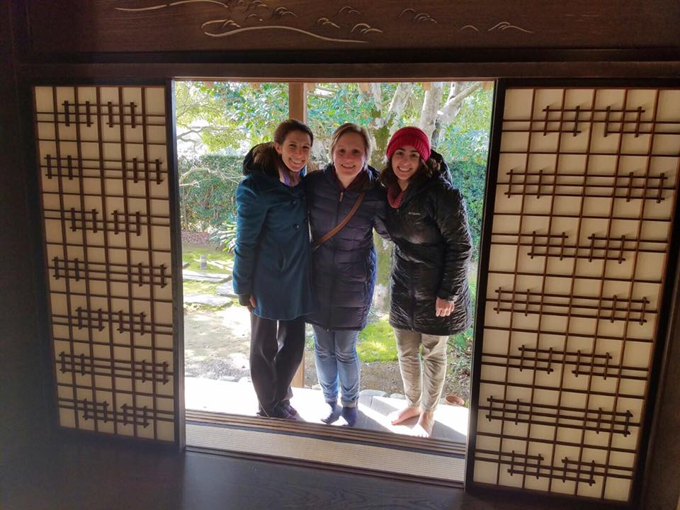 Alyson & friends smiling through a door at an old samurai temple in Nagasaki.