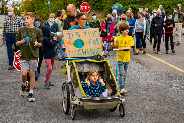 Family at a climate rally with child and sign 'Its time for change'.