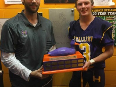 Jordan Travis and Defensive Coordinator Ed Shrubsole with the Cottage Cup Trophy; Travis set a Varsity team record with four interceptions. (Photo by Jason Romisher)