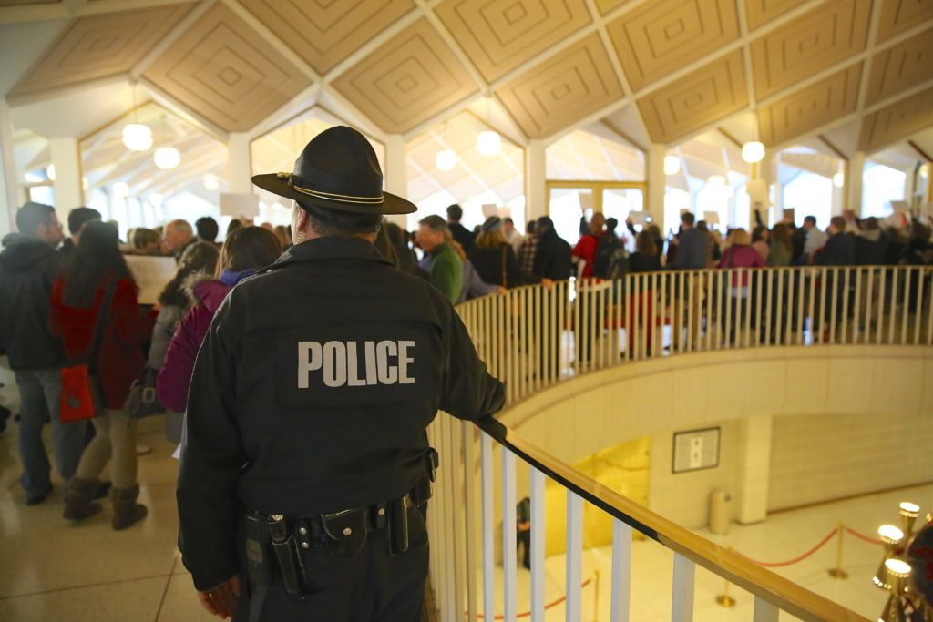 A member of the General Assembly's police force observes protesters demonstrating Thursday at the legislative building. The protesters disrupted sessions in the House and Senate. (CJ photo by Don Carrington)