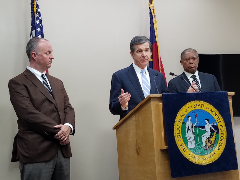 Gov. Roy Cooper discussed his House Bill 2 compromise earlier in February as Rep. Darren Jackson (left) and Sen. Dan Blue look on. (CJ photo by Barry Smith)