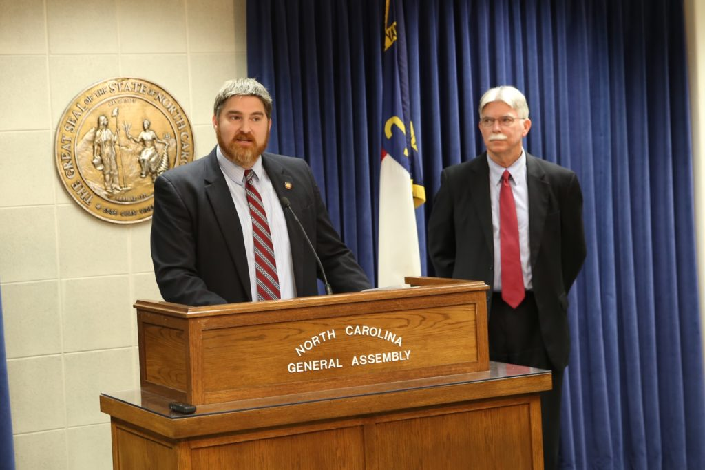 Reps. Chris Millis, R-Pender (at podium), and Jeff Collins, R-Nash, on Thursday announce the total tax subsidies provided renewable energy companies. (CJ photo by Don Carrington)