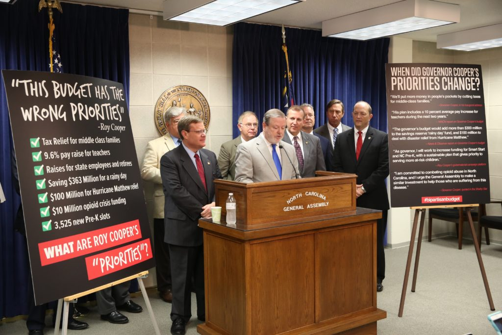 Senate leader Phil Berger (at podium) and House Speaker Tim Moore (at left), along with other legislative leaders, urge Gov. Roy Cooper to sign the 2017-19 General Fund budget at a June 2017 news conference. (CJ photo by Don Carrington)