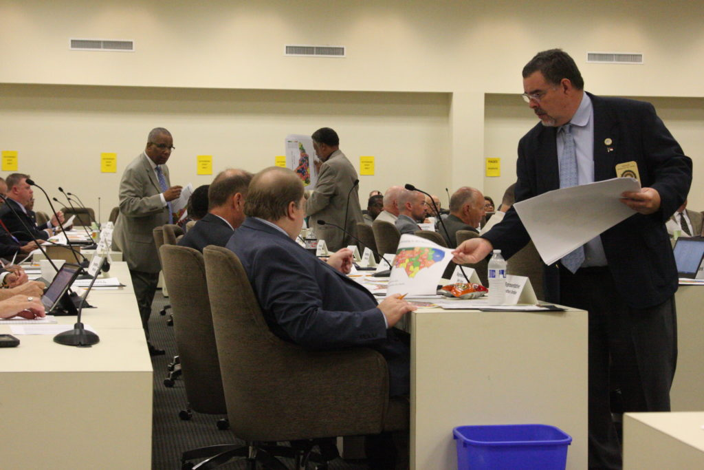 Sergeants-at-arms distribute copies of legislative district maps at an early August meeting of the joint legislative redistricting committee. (CJ photo by Dan Way)