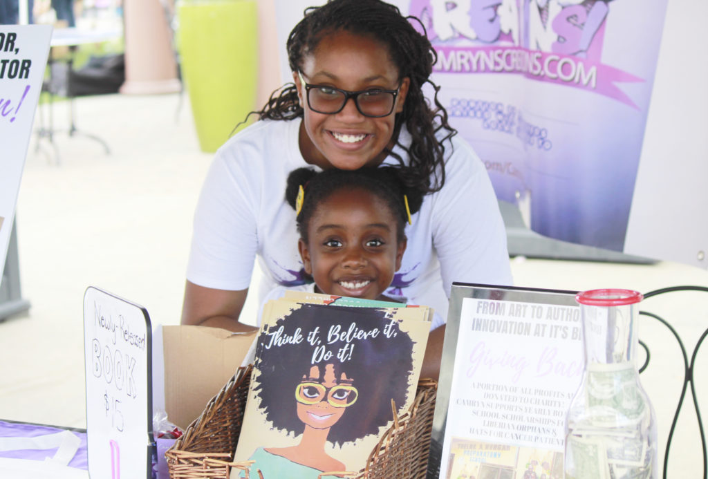 Fourteen-year-old artist Camryn Green, shown here with her young intern, donates a portion of every sale to a scholarship fund for Liberian orphans. (CJ Photo by Kari Travis)