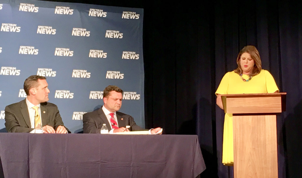 Moderator Loretta Boniti of Spectrum News (at lectern) queries (from left) Reps. Greg Meyer, D-Orange, and Jeff Elmore, R-Wilkes, at an Oct. 16 Hometown Debate in Burlington sponsored by the N.C. Institute of Political Leadership. (CJ photo by Lindsay Marchello)